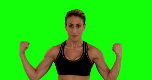 Mujer estupenda del ajuste que dobla sus brazos almacen de metraje de vídeo