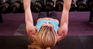 Mujer estupenda del ajuste que miente en pesas de gimnasia de elevación del banco en el crossfit almacen de metraje de vídeo