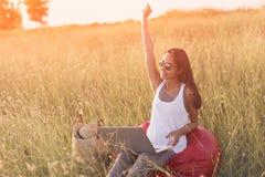 Mujer eufórica que busca trabajo con el ordenador portátil en un prado Foto de archivo libre de regalías