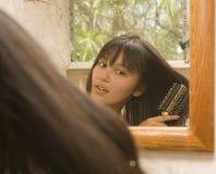 Mujer eurasiática joven que se peina el pelo fotos de archivo