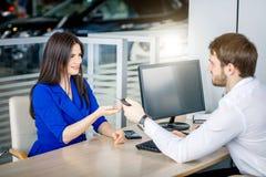 Mujer europea atractiva que recibe llaves del coche de agente de ventas del coche imagen de archivo
