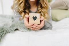 Mujer europea cauc?sica joven hermosa que lleva a cabo el coraz?n, el s?mbolo del amor fotos de archivo libres de regalías
