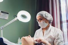 Mujer europea hermosa que tiene procedimiento facial de la piel aplicando una m?scara blanca del rejuvenecimiento del cosmetologi imagen de archivo libre de regalías