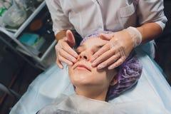 Mujer europea hermosa que tiene procedimiento facial de la piel aplicando una m?scara blanca del rejuvenecimiento del cosmetologi fotos de archivo libres de regalías