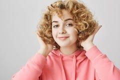 Mujer europea joven atractiva elegante con corte de pelo conmovedor rizado del pelo rubio mientras que sonríe y estando satisfech Imagen de archivo libre de regalías