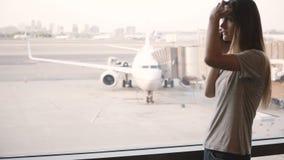Mujer europea joven que habla en el teléfono cerca de la ventana terminal de aeropuerto trastornada y frustrada después de vuelo  almacen de video