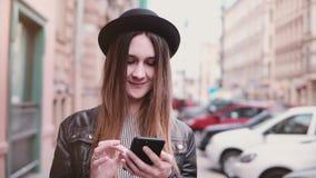 Mujer europea joven sonriente en sombrero elegante que camina a lo largo de la calle de la ciudad con un smartphone que mira la c almacen de video