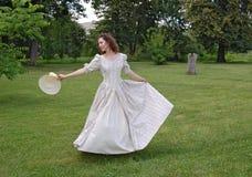 Mujer europea que baila y que toca su sombrero en vestido del vintage en parque Imágenes de archivo libres de regalías