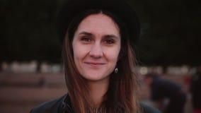 Mujer europea relajada positiva feliz joven en sombrero negro elegante con el pelo largo que mira la cámara, la sonrisa y la pres almacen de video