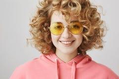 Mujer europea rizado-cabelluda atractiva de moda con las gafas de sol de moda que sonríe y que expresa amistosa y positiva Fotos de archivo