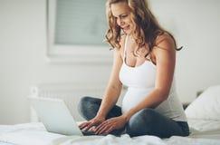 Mujer expectante embarazada que usa tecnología del hogar imagen de archivo libre de regalías