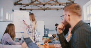 Mujer experta del negocio profesional que dibuja un diagrama de comercialización en el flipchart, empleados multiétnicos en el se metrajes