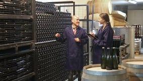 mujer experta que se coloca con el winemaker del tablero y del varón almacen de metraje de vídeo