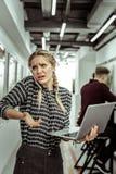 mujer expresiva Luz-cabelluda que está extremadamente ocupada en el trabajo fotografía de archivo