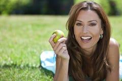 Mujer exterior comiendo un Apple y una sonrisa Fotos de archivo