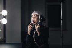 Mujer extraña que sostiene el vapor y que aplica el lápiz labial en vestuario Imagenes de archivo