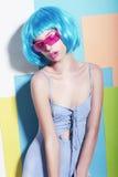 Mujer extravagante excéntrica en peluca azul diseñada y gafas de sol rosadas Fotos de archivo libres de regalías