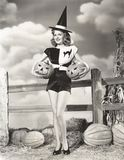 Mujer fascinante que lleva las calabazas talladas Imagenes de archivo