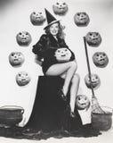 Mujer fascinante que se sienta entre las calabazas talladas Imagen de archivo