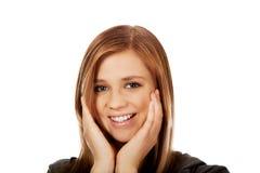 Mujer feliz adolescente que lleva a cabo ambas manos en mejillas Imagen de archivo libre de regalías