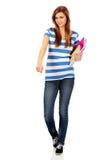 Mujer feliz adolescente que sostiene los libros de texto y que señala para algo Imagen de archivo