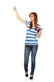 Mujer feliz adolescente que sostiene los libros de texto y que señala para algo Imagen de archivo libre de regalías