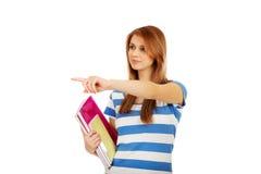 Mujer feliz adolescente que sostiene los libros de texto y que señala para algo Fotos de archivo libres de regalías