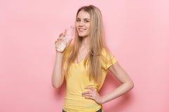 Mujer feliz adulta joven hermosa que sostiene la botella plástica con la pared rosada cercana derecha disponible y la sonrisa del Imágenes de archivo libres de regalías