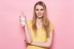 Mujer feliz adulta joven hermosa que sostiene la botella plástica con la pared rosada cercana derecha disponible y la sonrisa del Fotos de archivo libres de regalías