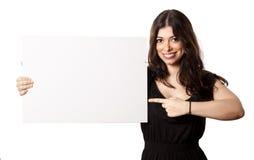 Mujer feliz aislada que señala en la muestra Fotos de archivo
