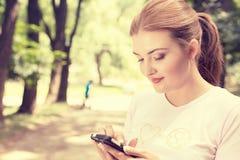 Mujer feliz, alegre, joven emocionada por lo que ella ve en mandar un SMS del teléfono celular Fotos de archivo libres de regalías