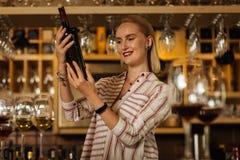 Mujer feliz alegre que lee la etiqueta de la botella fotografía de archivo libre de regalías