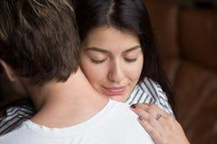 Mujer feliz aliviada que abraza al hombre, agradeciendo por ayuda, cierre para arriba Imagen de archivo libre de regalías