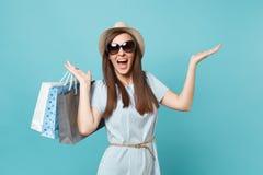 Mujer feliz atractiva de moda del retrato en el vestido del verano, sombrero de paja, gafas de sol que sostienen bolsos de los pa fotos de archivo