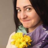 Mujer feliz atractiva del retrato que sostiene las flores Imágenes de archivo libres de regalías