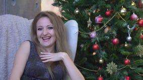 Mujer feliz atractiva joven que ríe, sonriendo y sentándose en fondo del árbol de navidad almacen de video
