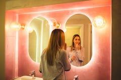 Mujer feliz atractiva que aplica maquillaje en el cuarto de baño de un restaurante imagen de archivo