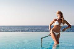 Mujer feliz atractiva que se coloca en piscina del infinito Fotografía de archivo
