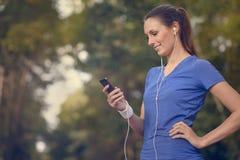 Mujer feliz atractiva que se coloca que escucha la música Imagen de archivo