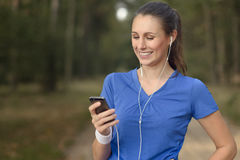 Mujer feliz atractiva que se coloca que escucha la música Imagen de archivo libre de regalías