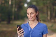Mujer feliz atractiva que se coloca que escucha la música Fotos de archivo libres de regalías