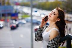 Mujer feliz bastante elegante de los jóvenes que habla en el teléfono elegante en la c Fotos de archivo libres de regalías
