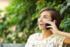 Mujer feliz casual en el teléfono en un parque Imagen de archivo