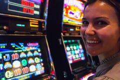 Mujer feliz cerca de las máquinas tragaperras Imágenes de archivo libres de regalías