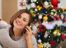 Mujer feliz cerca del árbol de navidad que hace llamada de teléfono Fotografía de archivo libre de regalías