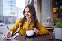 Mujer feliz con cacao de consumición del cuaderno en el café Imágenes de archivo libres de regalías