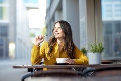 Mujer feliz con cacao de consumición del cuaderno en el café Foto de archivo