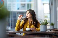 Mujer feliz con cacao de consumición del cuaderno en el café Imagen de archivo libre de regalías