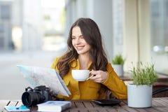 Mujer feliz con cacao de consumición del mapa en el café de la ciudad Fotos de archivo libres de regalías