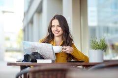Mujer feliz con cacao de consumición del mapa en el café de la ciudad Foto de archivo